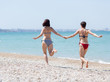 Two women in swimsuits running holding hands along beach