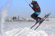A male athlete engaged in snow kiting on the ice of a large snowy lake. He performs the jump. Winter sunny frosty day. Close-up.