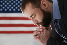 Man Praying On American Flag B...