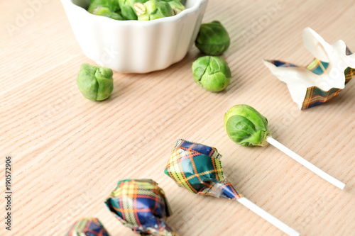 Photo Brussel sprouts with lollipop sticks in candy wrappers on table