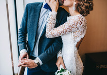 Wedding Couple, The Bride Holding The Groom By The Shoulder And A Wedding Bouquet Of Chamomiles