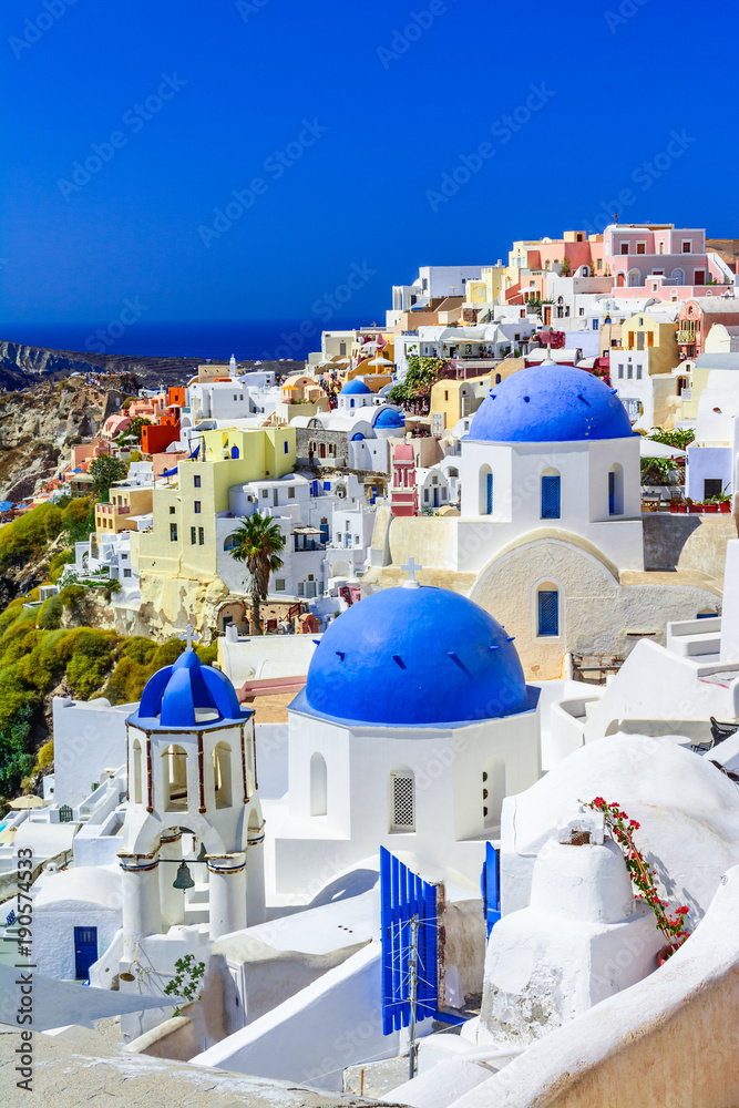 Fototapety, obrazy: Oia town, Santorini island, Greece at sunset. Traditional and famous white houses and churches  with blue domes over the Caldera, Aegean sea.