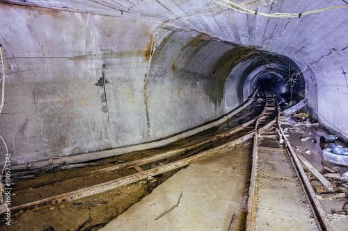 Plakat Bifurkacja zardzewiałej kolejki wąskotorowej. Tunel w opuszczonej kopalni. Obróć tunel. Światło z kolei.