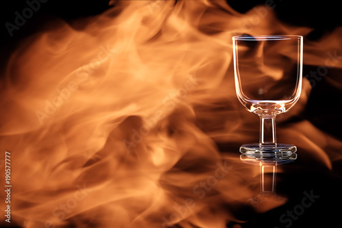 Stampa su Tela An empty glass of port or sherry in the fire flames.