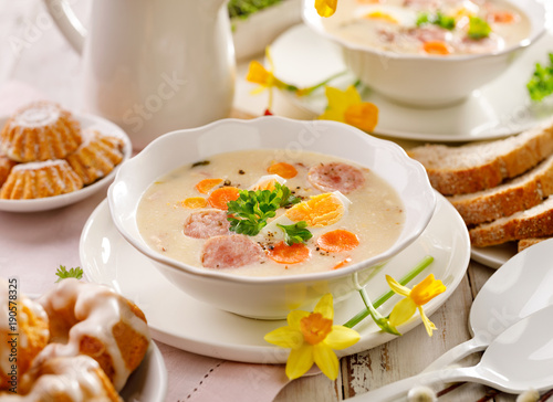 Tuinposter Klaar gerecht White borscht, polish Easter soup with the addition of white sausage and a hard boiled egg in a ceramic bowl. Traditional Easter dish in Poland