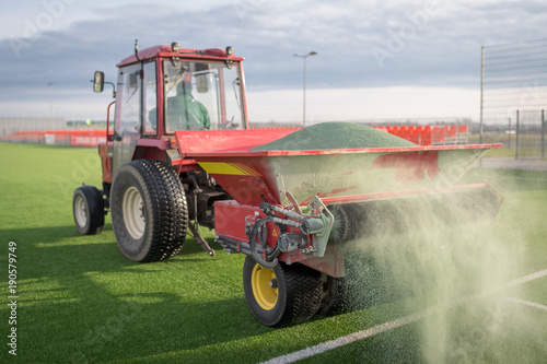 Fotografia  Pouring infill granules in to a football pitch with artificial grass