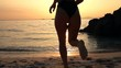 Silhouette of sexy young woman running on beach into sea during sunset, slow motion