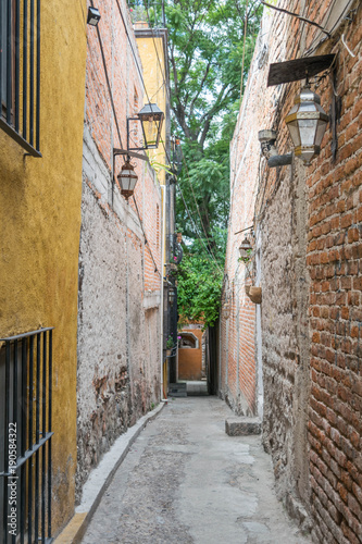Canvas Prints Narrow alley A narrow, charming alleyway with stone and brick walls on either side, and a few lanterns, in San Miguel de Allende