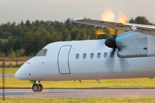 Fotografia, Obraz  Airplane with turboprop engine with propeller in motion taxing on runway, close