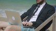 Businessman is typing business email on the beach. Man is sitting on comfortable deckchair with his brand-new laptop on the knees and working. Male professional is in black jacket, tie and blue shorts