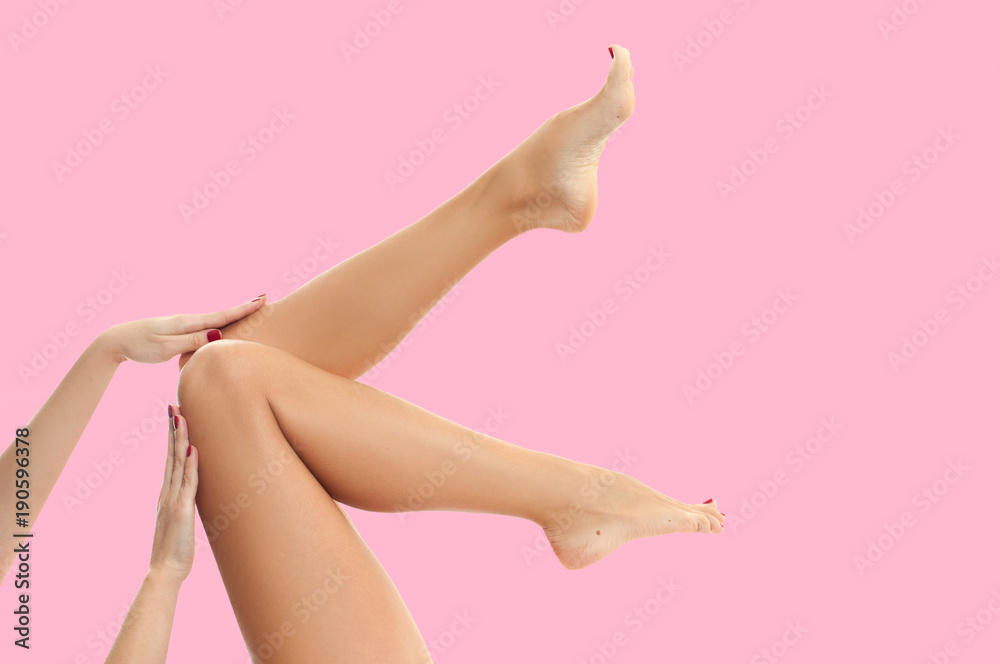 Fototapeta Woman's legs with smooth skin after depilation on pastel background.
