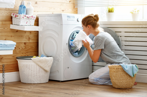 Happy housewife woman in laundry room with washing machine Wallpaper Mural