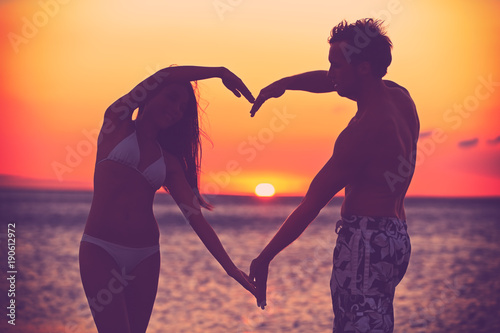Papiers peints Corail Love at sunset couple making heart shape with arms holding hands together on romantic honeymoon summer travel vacation. Lovers silhouettes. Valentine day symbol. Woman and man celebrating love.