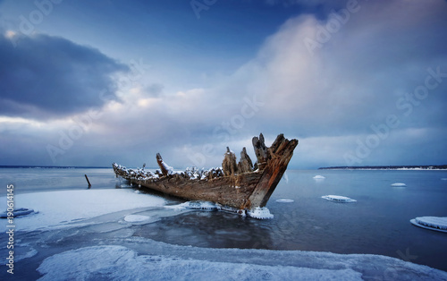 Cuadros en Lienzo Old wooden shipwreck in ice at sea. Winter on the water at night