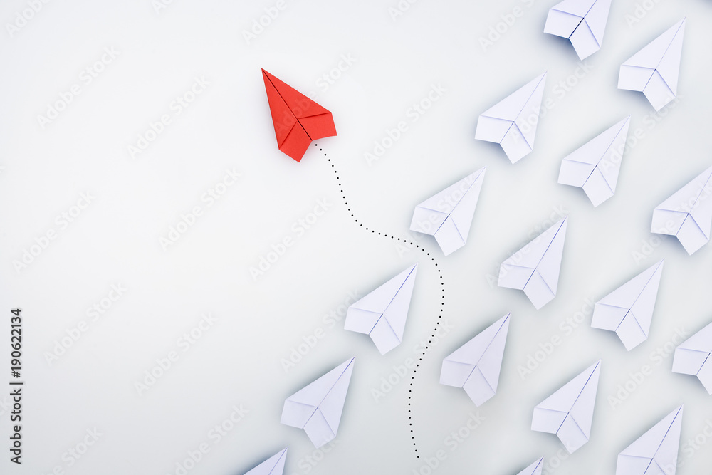 Fototapeta Group of paper planes in one direction and with one individual pointing in the different way. Business concept for innovative solution.