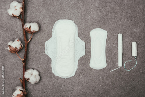 Fotografie, Obraz  top view of arrangement of cotton twig, menstrual pads and tampons on grey surfa
