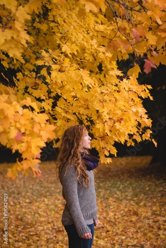 Thoughtful woman standing in the autumn forest