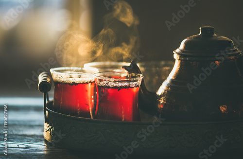 Deurstickers Thee Traditional hot steaming Turkish tea in tulip glasses with copper pot in vintage tray