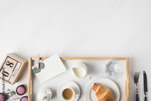 Fototapeta flat lay with cup coffee and croissant for breakfast on tray on white tabletop obraz