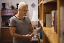 Senior Woman Selecting A Book