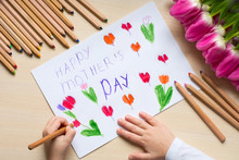 """Little Boy Paints Greeting Card For Mom On Mother's Day With The Inscription """"Happy Mother's Day"""". Top View"""