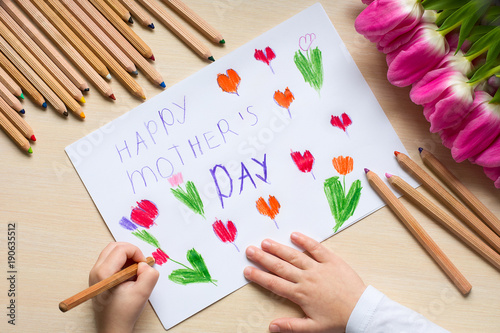 "Little boy paints greeting card for Mom on Mother's Day with the inscription ""Happy mother's day"". Top view"