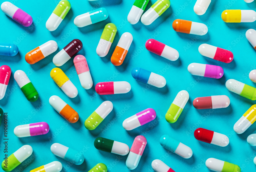 Fototapeta different color pills on blue background. Drugs and medicines