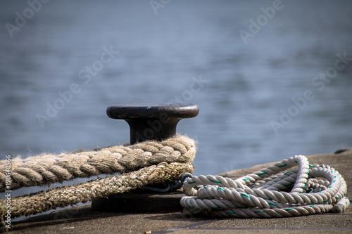 Ship mooring ropes secured around a port bollard Wallpaper Mural