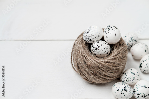 Quail easter eggs in nest on white table with copy space. Spring, Easter or healthy organic food concept.