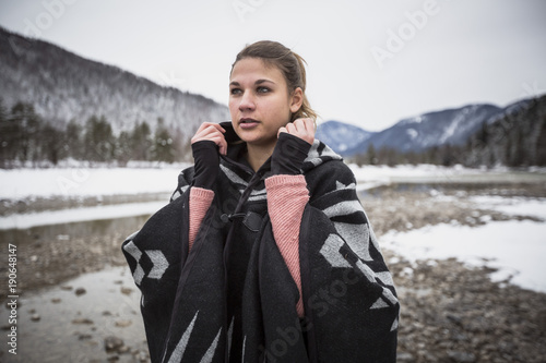 Young woman standing at a river in winter