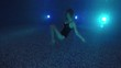 Dark Night. Beauty young woman swim under water in swimming pool to lights. Underwater view happy diving girl with long hair smiling and waving at camera wearing black fashion swimsuit