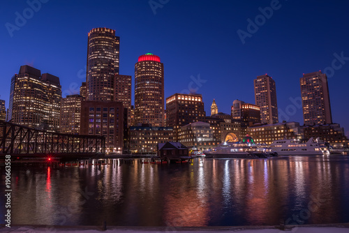 Sticker - Night view of the city, skyscrapers in the lights. Skyscrapers on the shore of the bay, lights reflected in the water, boats at the pier. Boston. USA.