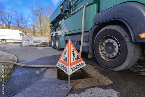 Tuinposter Kanaal Warnschild für Kanalreinigung steht neben dem Spülwagen am Strassenrand
