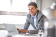 Portrait of smiling young businessman using laptop in office