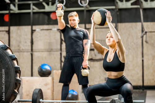 Spoed Foto op Canvas Fitness Young athletic couple in black sports wear training with weights and ball in the crossfit gym