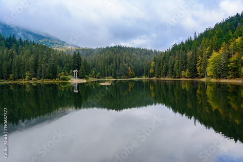 Foto op Plexiglas Meer / Vijver View of Synevir high-altitude lake by autumn day. The leaf fall forest is reflected in water of lake.