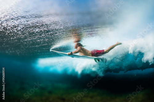 Young surfer dives under the ocean wave with surf board and performs trick named in surfing as a Duck Dive Canvas Print