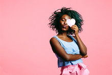 Woman With Blue Curly Hair Blowing A Kiss And Holding A Pink Heart Covering Her Eye
