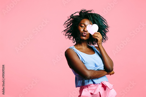 Fotografie, Tablou woman with blue curly hair blowing a kiss and holding a pink heart covering her