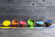 Festival Of Colors. Bright Colors For Holi Festival. Colorful Holi Paint In Coconut Shells On A Wooden Table With Copy Space. Creative Shoot.
