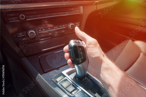 Fototapeta man's hand on an automatic gearbox