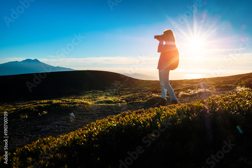 Fototapeta Hiker takes pictures from top of the mountain during sunset using the best of the golden hour obraz na płótnie
