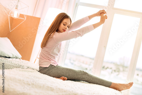 Supple Body Charming Teenage Girl Sitting On The Bed And Stretching Herself In The Morning Having Woken Up In The Morning Buy This Stock Photo And Explore Similar Images At Adobe