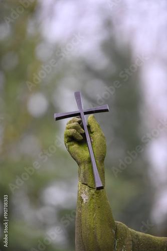 Zdjęcie XXL Chrześcijański krzyż w zwietrzałej dłoni rzeźbiarza grobowca