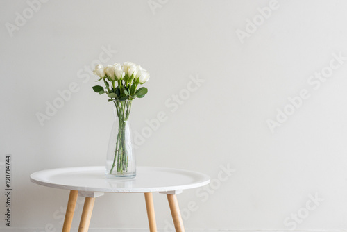 White Roses In Glass Vase On Small White Table Against Beige Wall