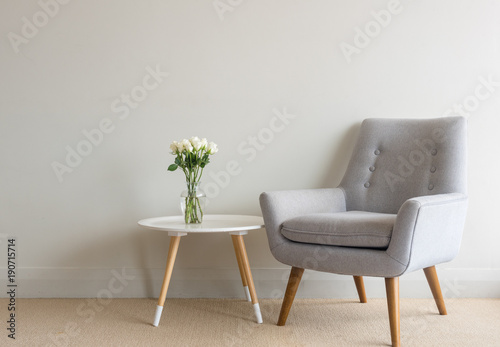 Valokuva  Retro armchair and small round table with white roses in glass vase against beig
