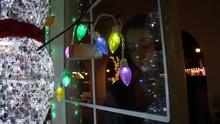 Transgender Teen Looking Through Window Full Of Christmas Decor