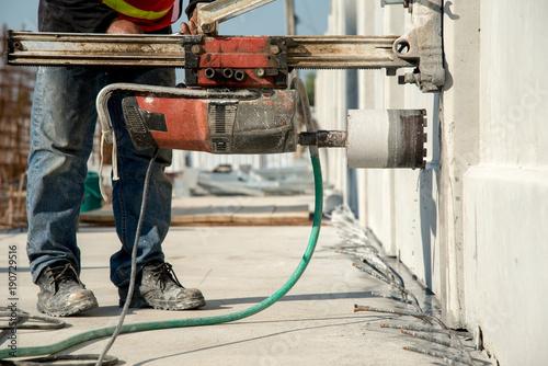 Construction worker coring concrete