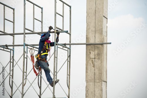 Obraz na plátně Construction worker working on scaffolding in construction site