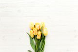 Fototapeta Tulipany - yellow tulips isolated on a white, wooden background. lay flat, top view